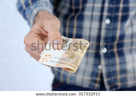 Man holding euros in hand - stock photo