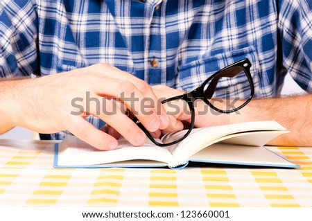 Man holding eye wear on the book - stock photo