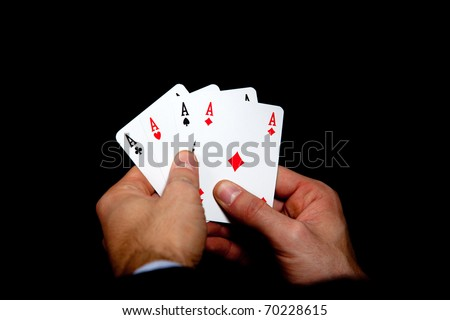 Man holding four aces in hands isolated on black background - stock photo