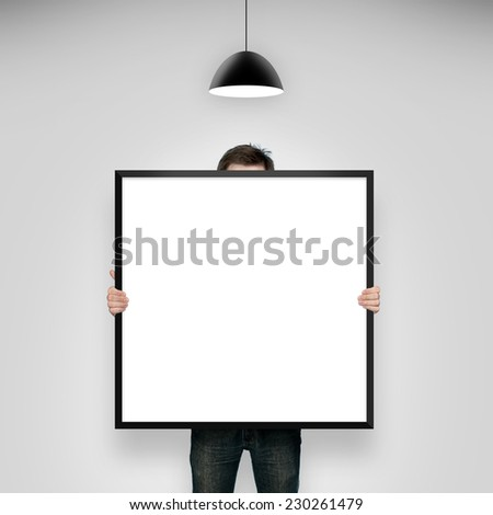 man holding frame in room with lamp - stock photo