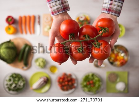 Man holding fresh juicy tomatoes hands close up, vegetables and food ingredients on background, top view - stock photo