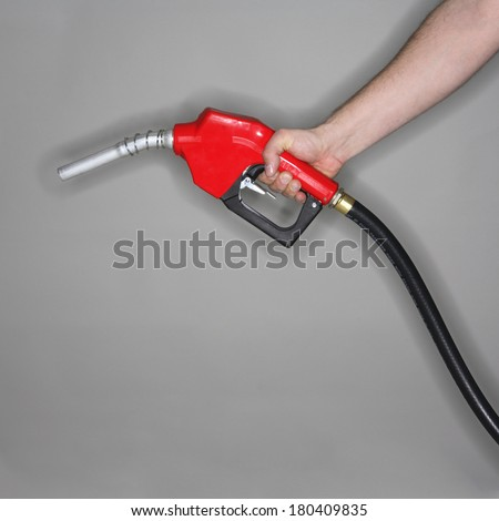 man holding gas hose with red nozzle on grey background  - stock photo