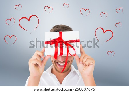 Man holding gift against grey vignette - stock photo