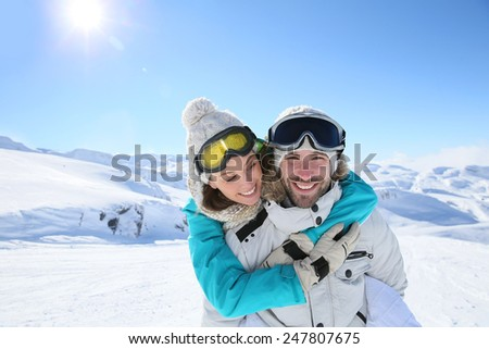Man holding girlfriend on his back at the top of mountain - stock photo