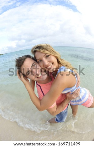 Man holding girlfriend on the beach - stock photo