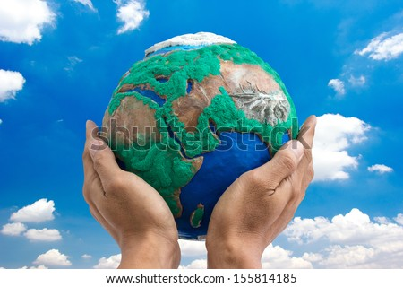 man holding globe made from clay on his hands  with blue sky background - stock photo