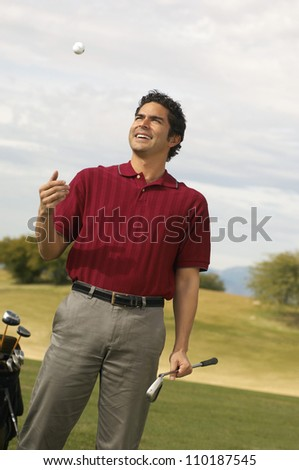 Man holding golf club while tossing ball - stock photo