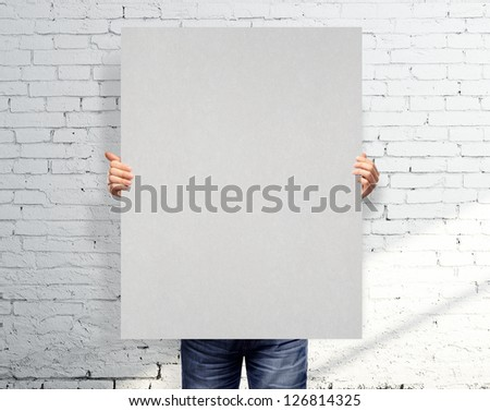 man holding gray poster in loft