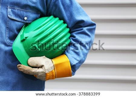 Man holding green helmet close up, shallow dof - stock photo