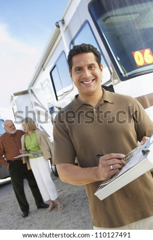 Man holding guide book with passengers in the background - stock photo