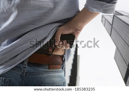 Man holding gun against an skyscraper background  - stock photo