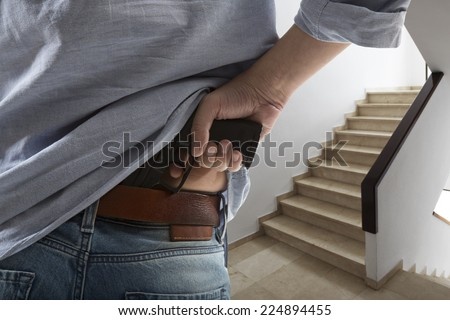Man holding gun against an stairs background - stock photo