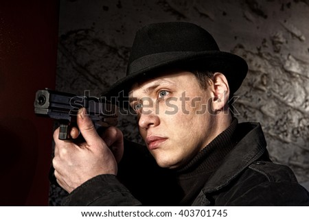 Man holding gun against an wall background - stock photo