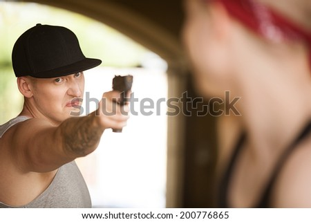 man holding gun and pointing at person. criminal and victim closeup view looking at each other - stock photo