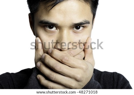 Man Holding hands over mouth copying the common phrase see no evil, hear no evil, speak no evil