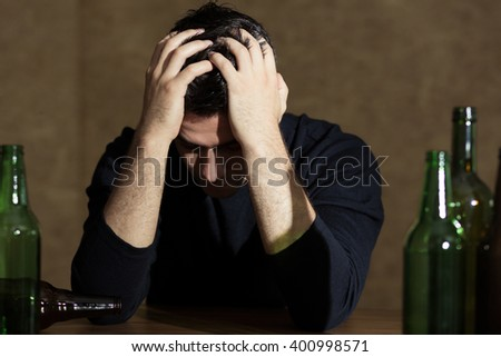 Man holding head in his hands, sitting beside bar table, empty bottles next to him - stock photo