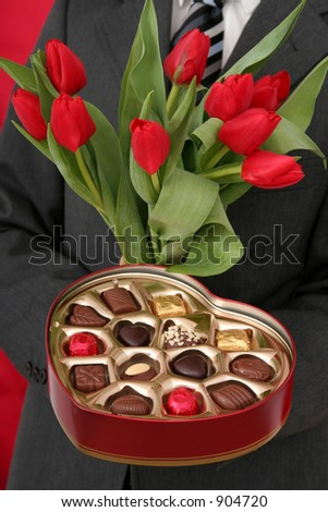 Man Holding Heart Shaped Box of Candy and Red Tulips - stock photo