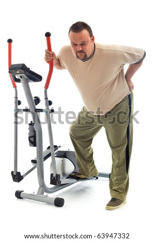 Man holding his aching back leaning on exercising device - isolated - stock photo
