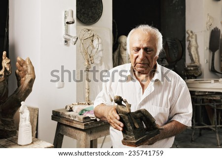 Man holding his artwork in sculptor workshop - stock photo