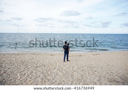man holding his baby at a beach.