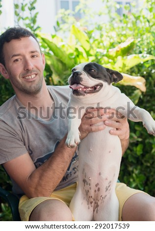Man holding his dog, a beautiful French bulldog female - stock photo