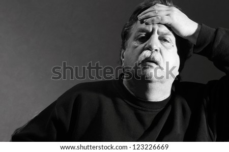 man holding his hand to his forehead - stock photo