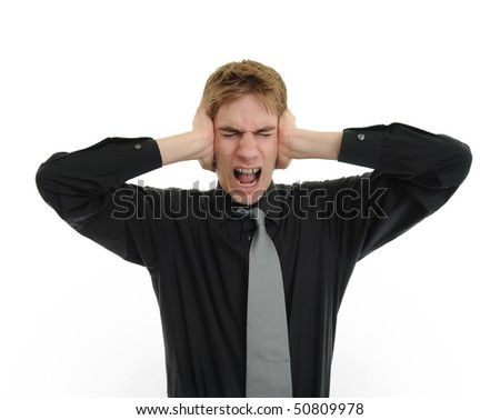 Man holding his hands up to his ears trying to mute all the voices he hears - stock photo