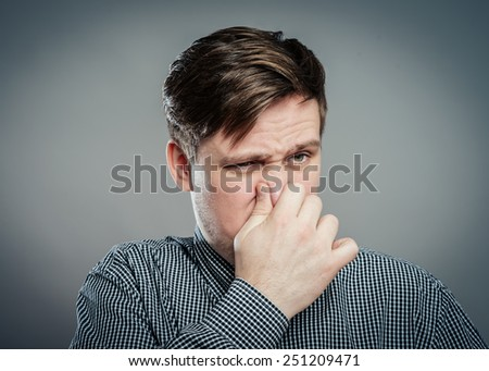 Man holding his nose against a bad smell - stock photo