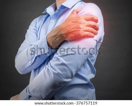 man holding his shoulder in pain - stock photo