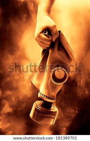 Man holding in hand a gas mask - stock photo