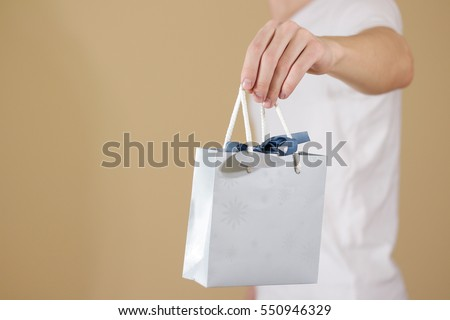 Man holding in hand blank blue paper gift bag mock up. Empty package mockup hold in hands isolated. Consumer pack ready for logo design or identity presentation. Product packet handle