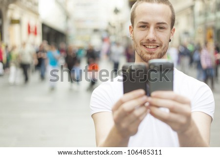 Man holding in hands two mobile phone, blurred city street and people in background - stock photo