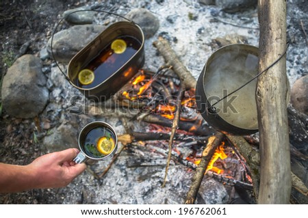 man holding in his hand metal mug with tea, mint and lemon, and next to the fire heats the water in the boiler.  - stock photo