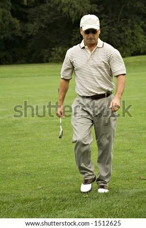 Man holding 8 iron, deeply contemplating last golf shot. - stock photo