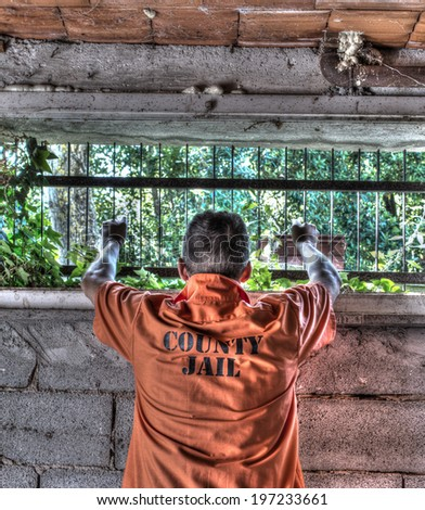 man holding jail bars - stock photo
