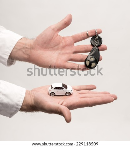 Man holding keys and small car on a gray background