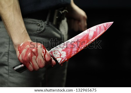 Man holding knife with blood dripping - stock photo