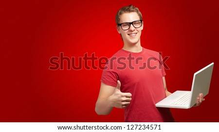 Man holding laptop with thumbs up isolated on red background