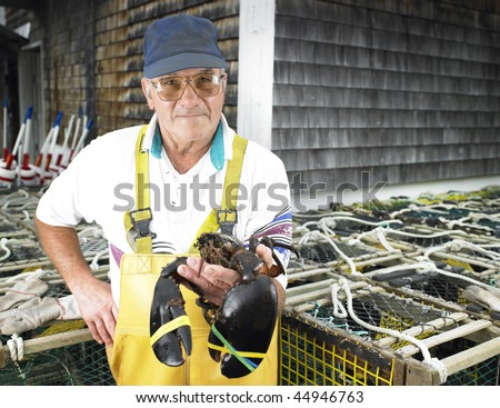 Man holding lobster and facing the camera.  Lobster traps in the background. Horizontal shot. - stock photo