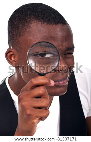 Man Holding Magnifying Glass Looking Close into the Matter: Large Eye in Focus - stock photo
