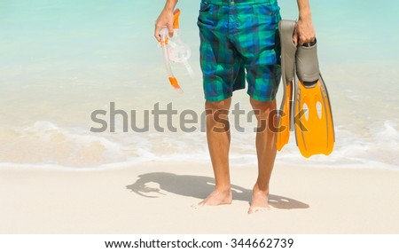 man holding mask and flippers for swimming on the background the azure sea