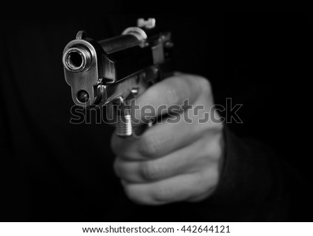 Man holding metal gun on a dark background - stock photo