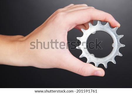 Man holding metallic cogwheel in his hand on gray background - stock photo