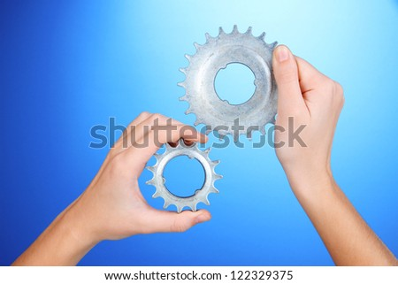Man holding metallic cogwheels in his hands on blue background - stock photo