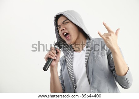 man holding microphone with the hand sign - stock photo