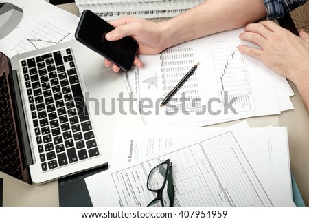 Man holding mobile phone in home office whith laptop and paperwork