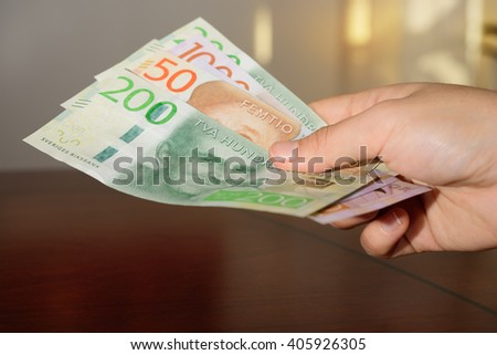 Man holding new Swedish bank notes - stock photo