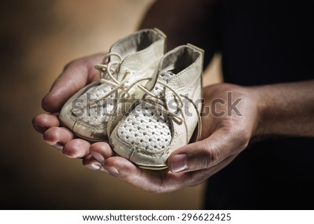 Man holding old and worn leather baby shoes in his hands. - stock photo