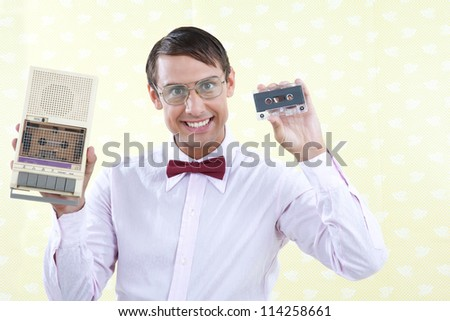 Man holding old audio cassette and player.