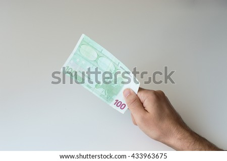 Man holding one hundred Euro banknote in his hands - stock photo
